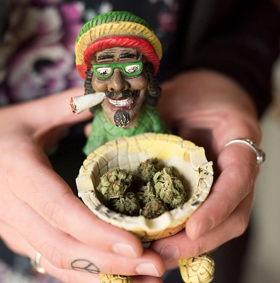 Woman holding container with Cannabis bud