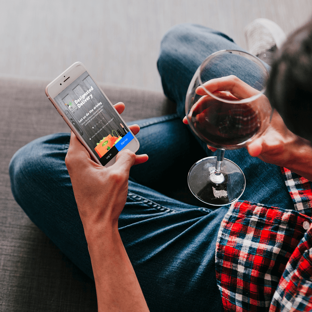 man using alcohol delivery app while drinking wine